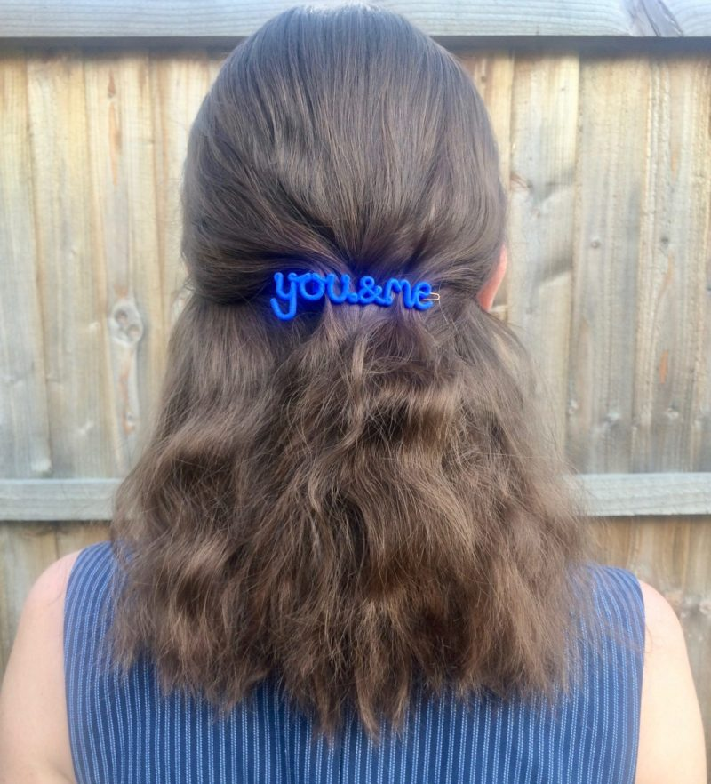 Hair clip that says the words 'You & Me' in blue.