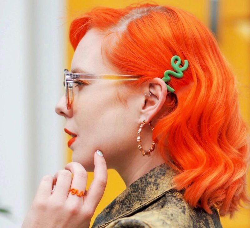 Green 'Me' hair clip, on orange hair.