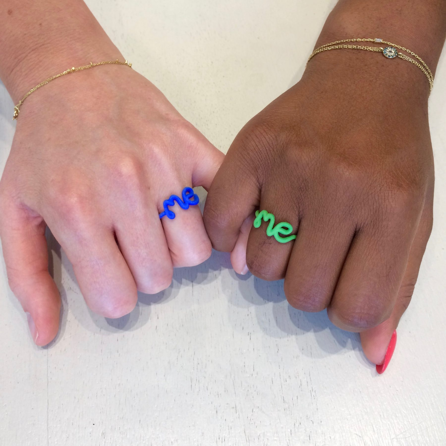 Me rings worn by friends holding hands